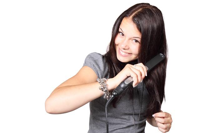 dívka při žehlení vlasů