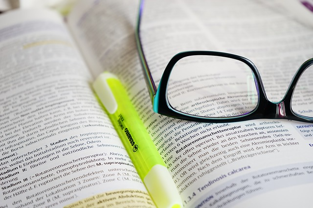 učebnice, brýle a propiska