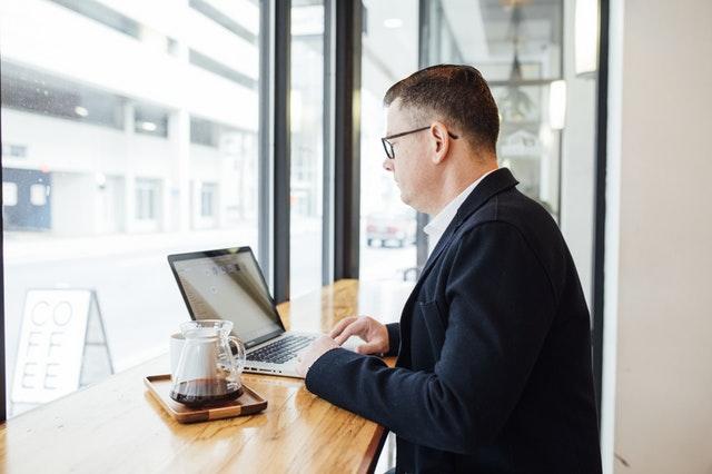 Muž sediaci v miestnosti s presklenými  stenami