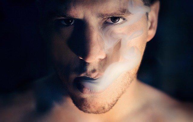 Mužovi ide z úst cigaretový dym