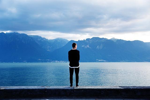 Mladý muž stojí pri jazere a pozerá sa do diaľky