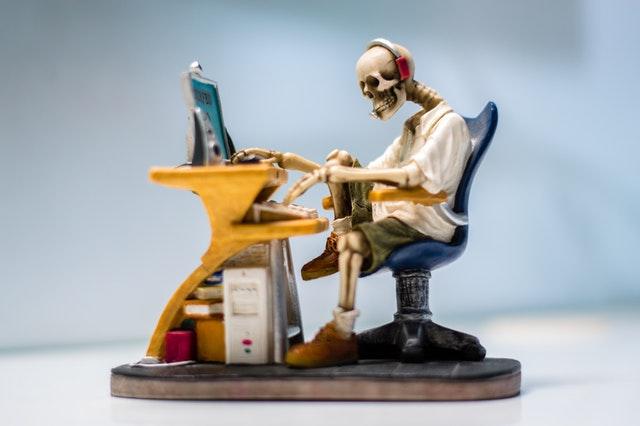 Figúrka kostry sedí pri stole a pracuje na počítači